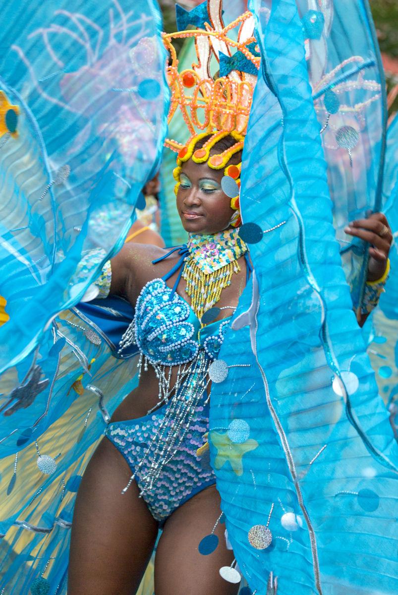 Victoria, Seychely  Tanečnice v překrásných modrozelených šatech tančí v ulicích Victorie, na přehlídce Mezinárodního seychelského karnevalu