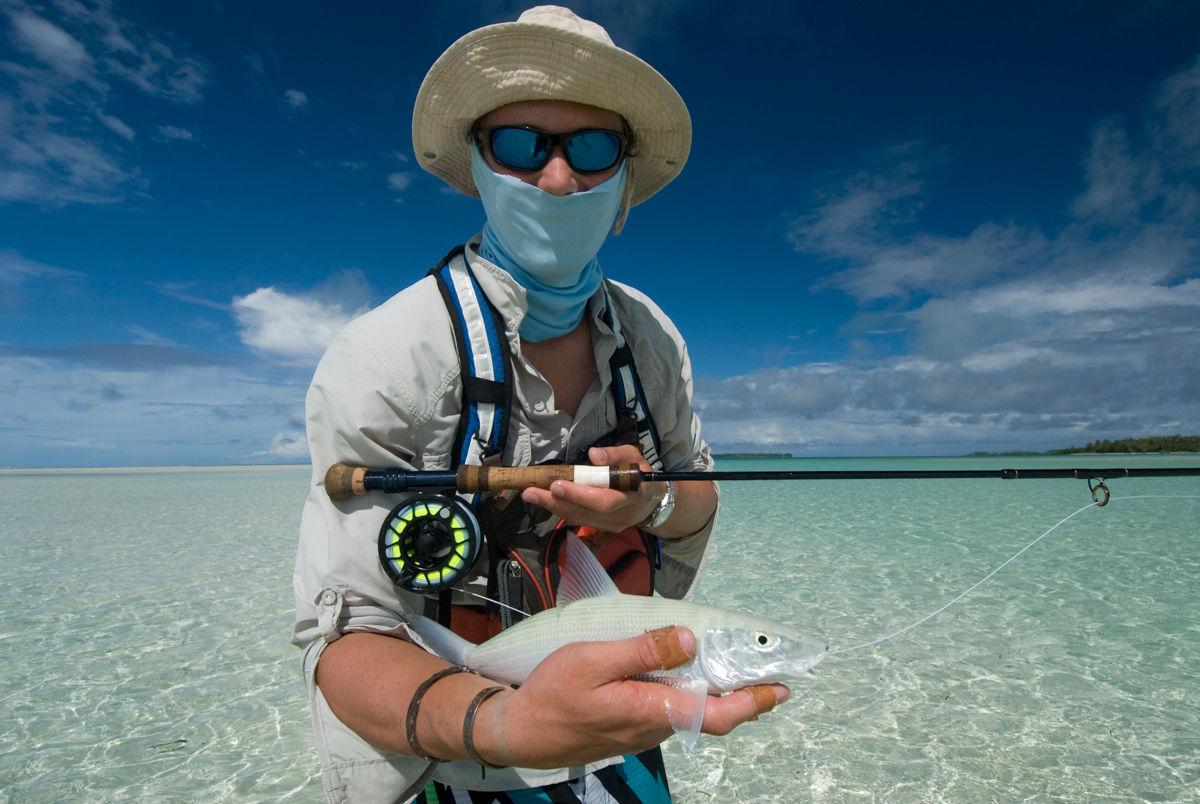 Rybář létajících ryb ukazuje svůj úlovek, bonefish.