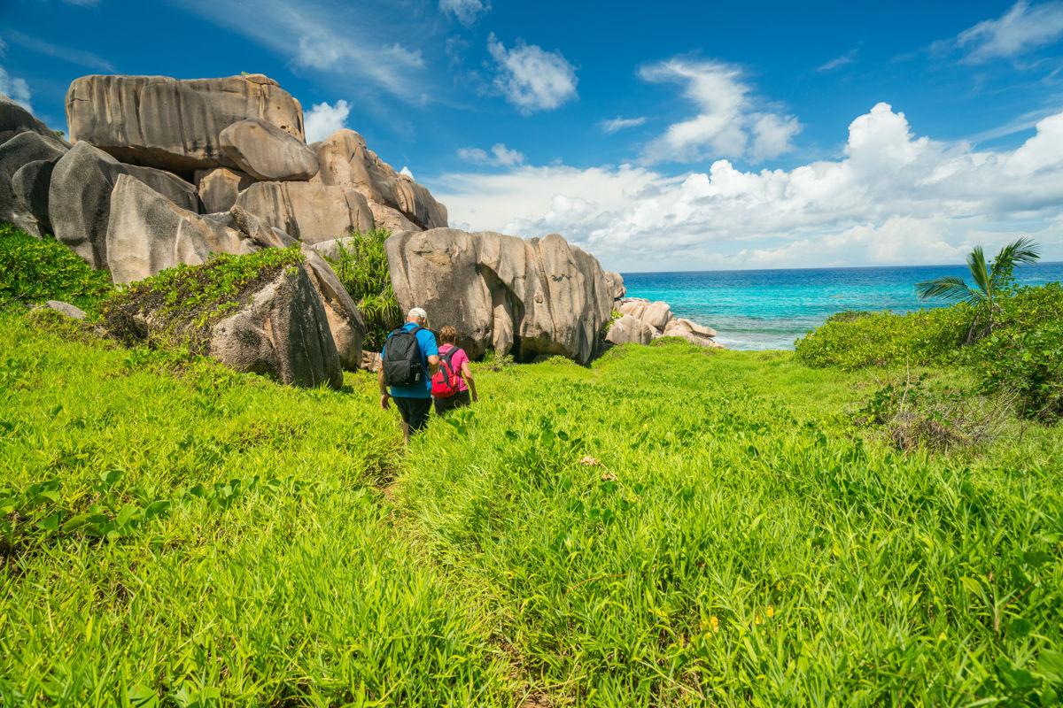 Dvojice aktivních seniorů kráčející ve vysoké trávě na seychelském ostrově.