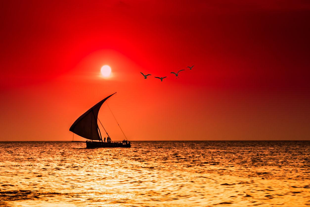 Silueta plaechetnice a mořského zálivu během překrásného západu slunce.