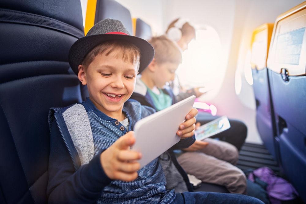 Happy kids travelling in plane. The kids are using technology to make the flight even more fun. They are playing video games on digital tablets. The girl in the background is wearing headphones and listening to the music.
